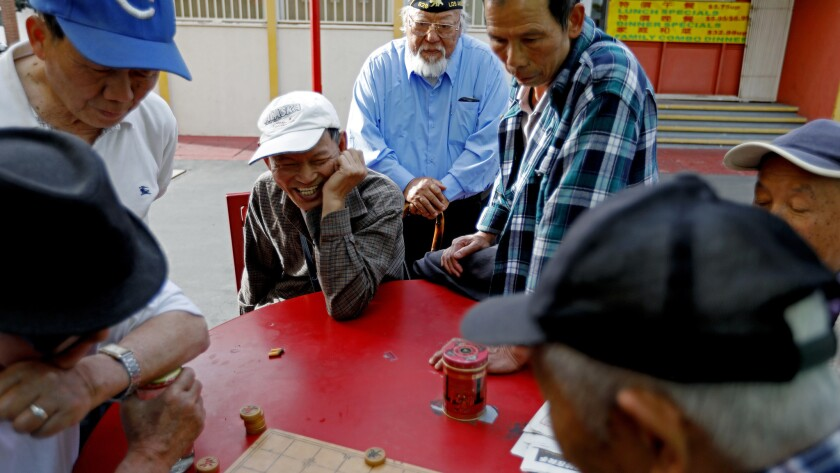 Jimmy Wong stops to watch a group of men play Chinese Chess while walking through Chinatown.