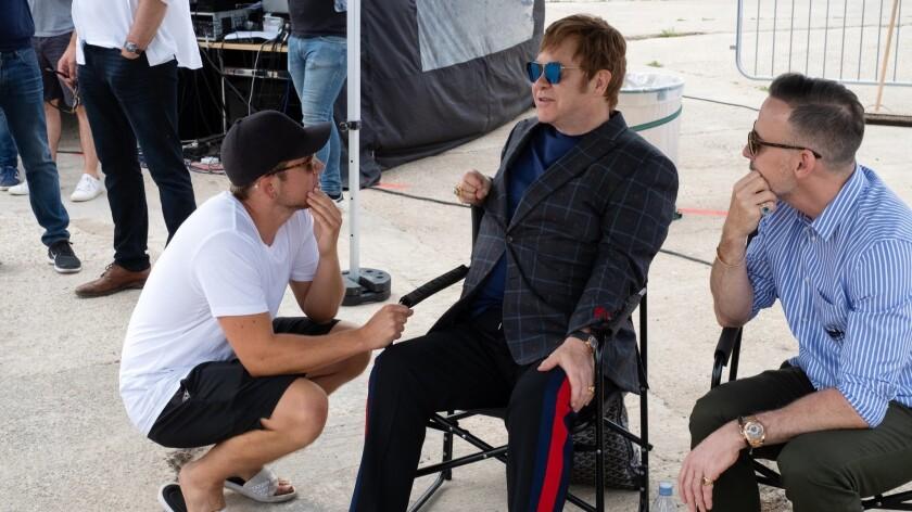 "(L-R)- Taron Egerton, Elton John and David Furnish on the set of ""Rocketman"" from Paramount Pictures"