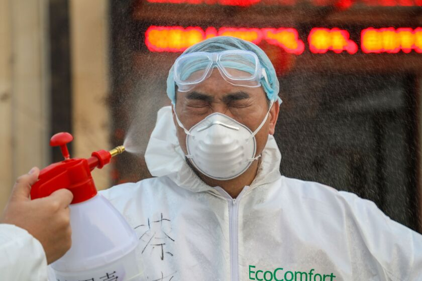 A doctor is disinfected by a colleague Feb. 3 at a quarantine zone in Wuhan, China.