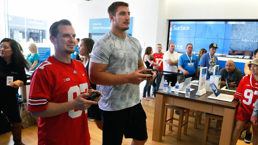 From left to right, Andrew Fulton, of San Marcos, plays a short game of Madden with Chargers rookie defensive end Joey Bosa at the Microsoft Store in Fashion Valley where fans showed up to meet Bosa Saturday