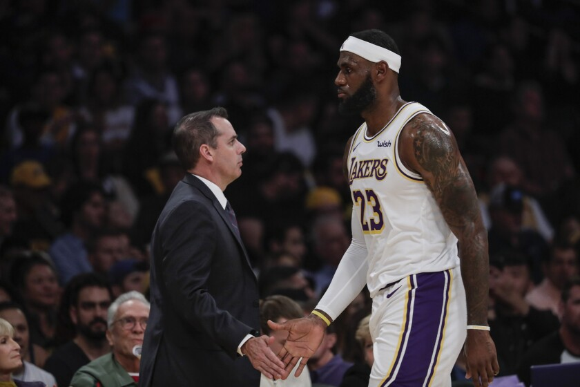Lakers coach Frank Vogel and forward LeBron James slap hands as the All-Star forward comes off the court during a break in play against the Warriors on Oct. 16, 2019.