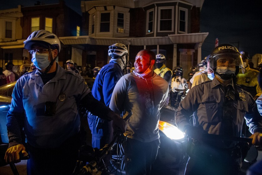 A person is handcuffed and detained by police in Philadelphia Oct. 28