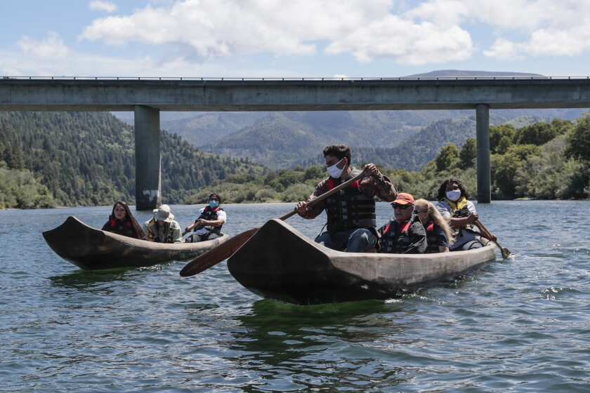 Klamath, CA, Thursday, June 10, 2021 - Yurok guides Zechariah Gabel, front, Sammy Gensaw, right and Jon-Luke Gensaw, left, paddle tourists along the Klamath River in traditional canoes hand crafted from Redwood trees. (Robert Gauthier/Los Angeles Times)