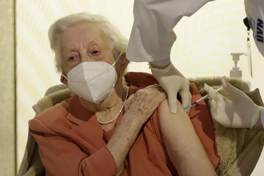 World War II veteran Emilie Repikova receives a COVID-19 vaccine at a military hospital.