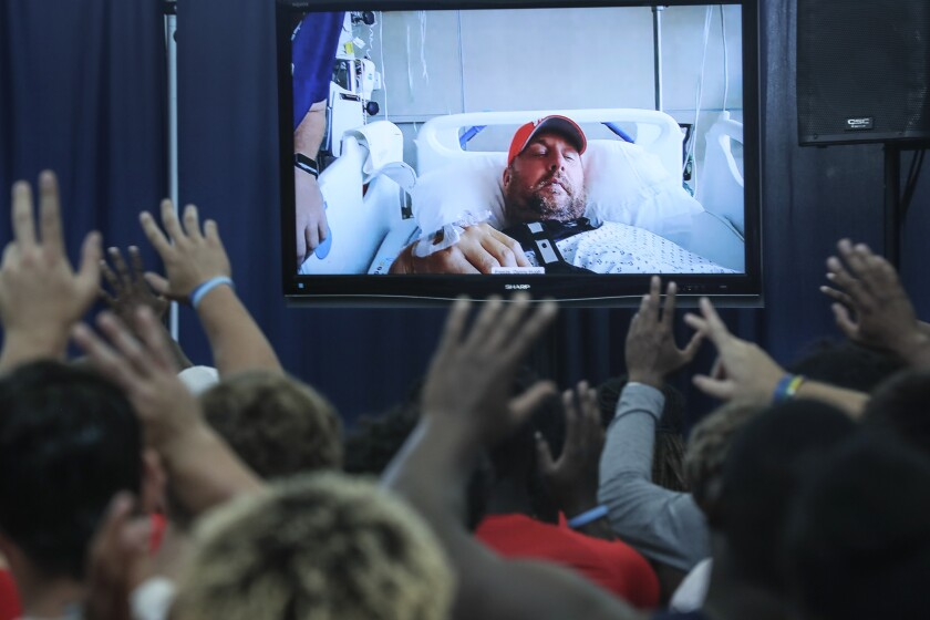 Liberty football players wave goodbye to coach Hugh Freeze at the conclusion of a video conference.