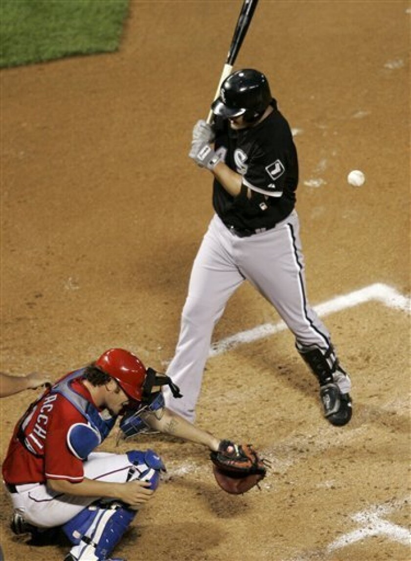 Chicago White Sox's Paul Konerko, top, and Texas Rangers catcher Jarrod Saltalamacchia, bottom, both react as Konerko is hit by a pitch from Brandon McCarthy in the second inning of a baseball game in Arlington, Texas, Saturday, May 2, 2009. (AP Photo/Tony Gutierrez)