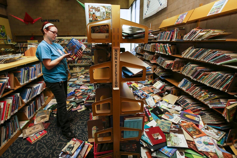 Shalyn Pineda, regional supervisor of Kern County's libraries, picks up books at Ridgecrest Library after Thursday's 6.4 earthquake dislodged bookshelves.