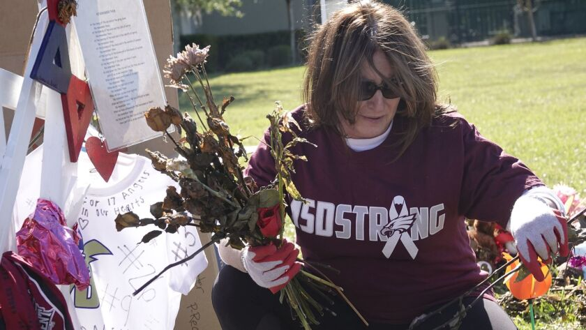 A volunteer tends a shrine to victims of the Parkland, Fla., mass school shooting.