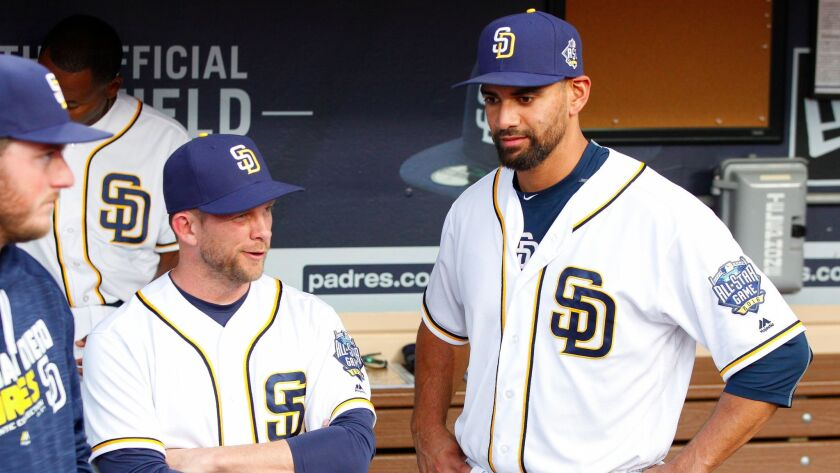 Padres manager Andy Green, left, talks to pitcher Tyson Ross in the dugout before the Padres' game against the Pirates at Petco Park in San Diego.