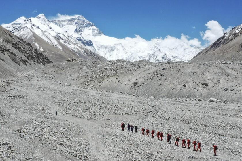 En esta imagen de archivo, distribuida el 16 de mayo de 2020 por la agencia noticiosa oficial china Xinhua, investigadores chinos caminan hacia el campo base del Everest, Qomolangma en tibetano. (Jigme Dorje/Xinhua vía AP, archivo)