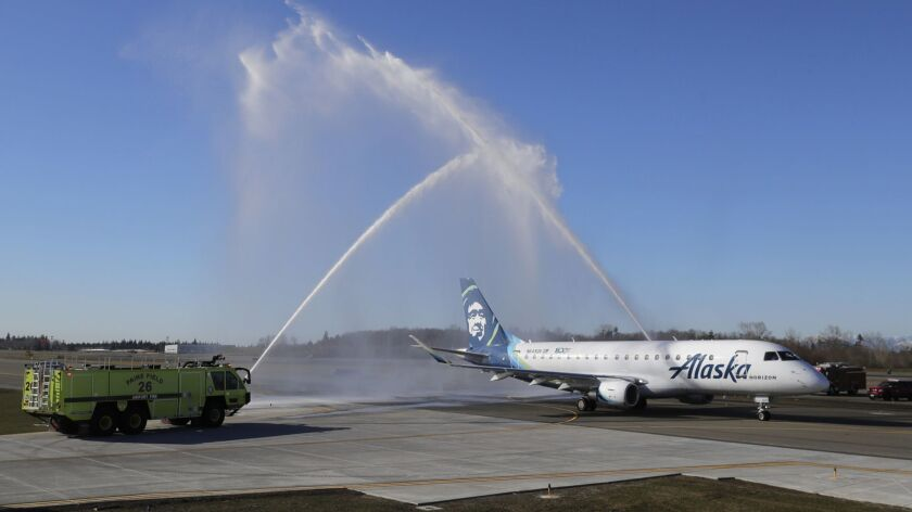 An Alaska Airlines Embraer 175 airplane gets a water-arch departure on Monday as it taxis for take-off for a flight to Portland, Ore., at Paine Field in Everett, Wash. The flight was the first flight on the inaugural day of commercial passenger service from the airport.