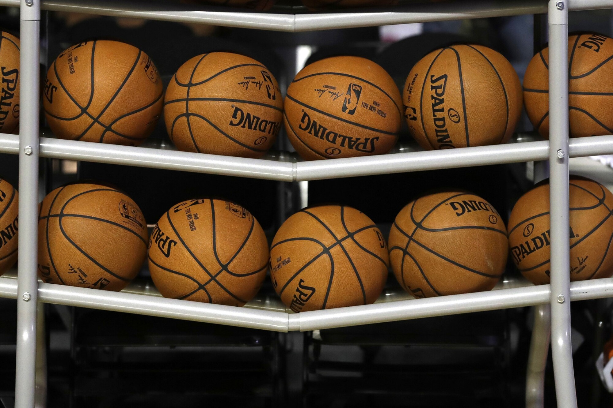 Basketballs sit in a rack on the court
