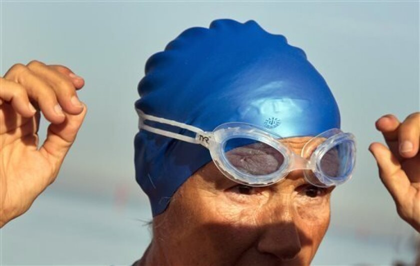 U.S. swimmer Diana Nyad, 64, adjusts her goggles before jumps into the water and start her swim to Florida from Havana, Cuba, Saturday, Aug. 31, 2013. Endurance athlete Nyad launched another bid Saturday to set an open-water record by swimming from Havana to the Florida Keys without a protective sh