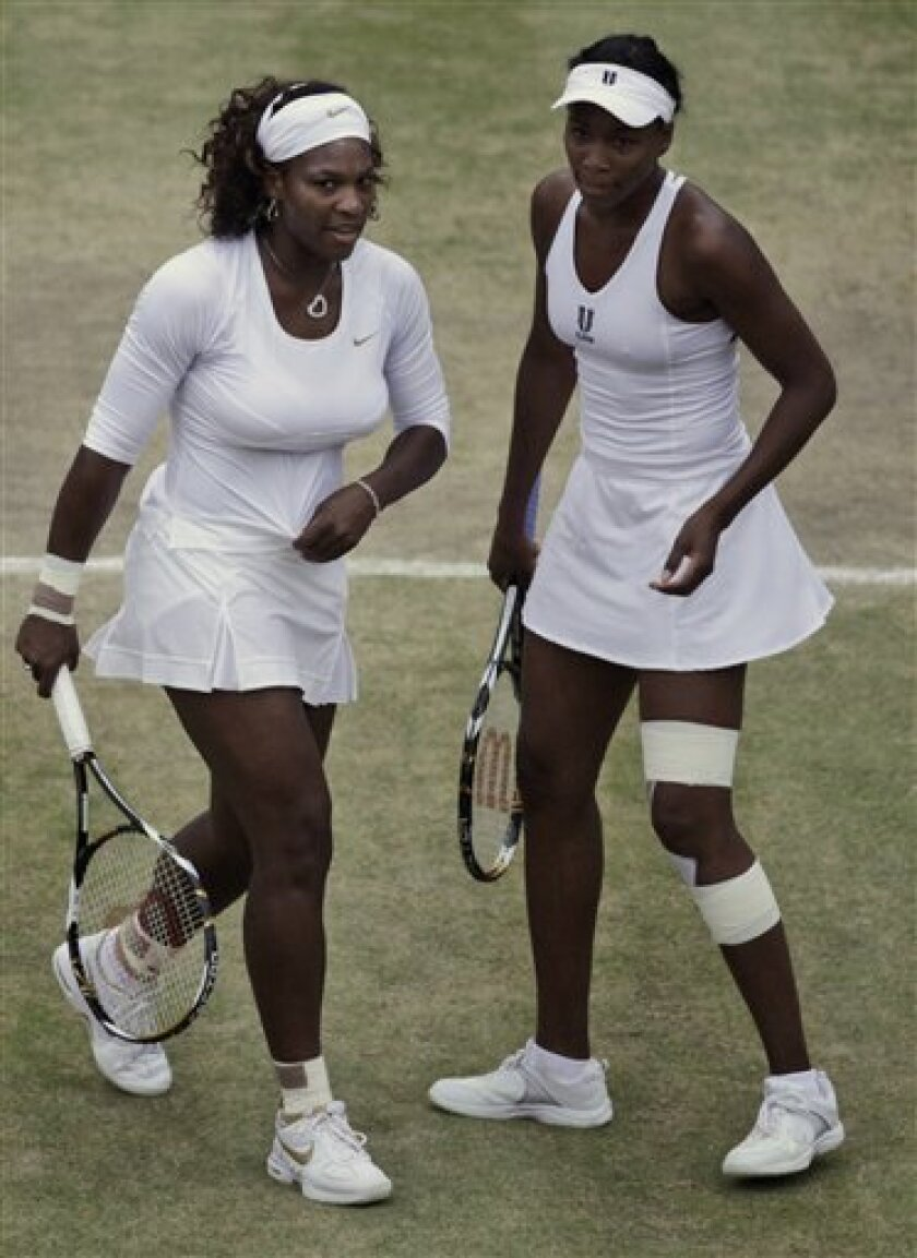 Serena, left and Venus, right Williams return speak while playing Cara Black of Zimbabwe and Liezel Huber of the U.S. during their doubles match at Wimbledon, Friday, July 3, 2009. (AP Photo/Anja Niedringhaus)