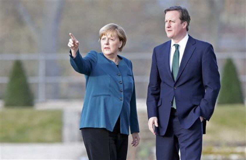German Chancellor Angela Merkel and Britain's Prime Minister David Cameron look on as they stroll inside the yard of the government's guest house Schloss Meseberg, 70 km (44 miles) north of Berlin April 12, 2013. (AP Photo/Pool/Fabrizio Bensch)