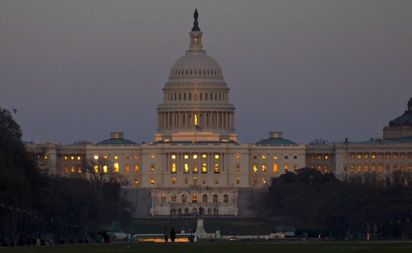 """This March 22, 2013, file photo shows the setting sun reflected in the windows of the U.S. Capitol in Washington. If there's one word that describes how Americans feel about politics these days, it's """"negative."""" Majorities disapprove of Congress and the president and say the nation is heading in the wrong direction. Few trust their political leaders to make the right decisions, and some polls suggest voters would like to see the whole lot turned out next November. (AP Photo/Alex Brandon)"""