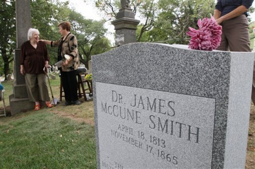 A flower lays atop the new tombstone of Dr. James McCune Smith, the nation's first professionally trained African-American doctor, as Smith's great-granddaughter Antoinette Martignoni, left, and Smith's great-great-granddaughter Judy Gerlitz share a moment during a ceremony honoring Smith, Sunday Sept. 26, 2010 at Cypress Hills Cemetery in the Brooklyn borough of New York. Smith's gravesite had been unmarked since his death in 1865. (AP Photo/Tina Fineberg)