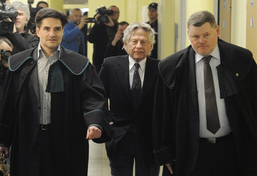 Filmmaker Roman Polanski, center, with his lawyers, arrives at the regional court in his childhood city of Krakow, Poland, Wednesday, Feb. 25, 2015. Polanski appeared in the court for a hearing concerning a U.S. request for his extradition over 1977 charges of sex with a minor. (AP Photo/Alik Keplicz)