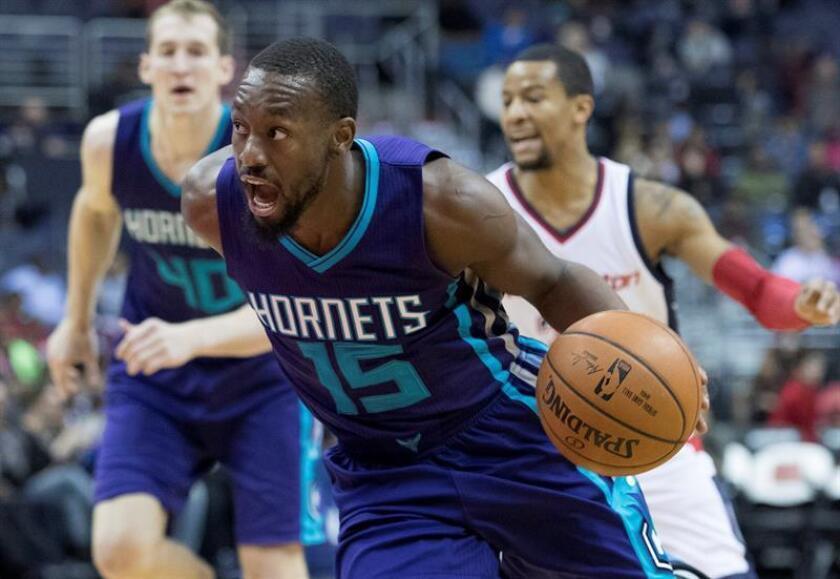 Kemba Walker (frente) de Charlotte Hornets avanza ante Washington Wizards hoy, miércoles 14 de diciembre de 2016, en juego de la NBA en Verizon Center en Washington (EE.UU.). EFE