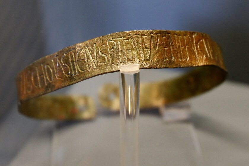 """This Monday, June 13, 2016 photo shows a bronze slave collar of the 5th century displayed at """"Made in Roma"""" exhibition at the Trajan's Markets site in Rome. In an ancient twist to today's Made-in-Italy labeling, Romans of some 2,000 years ago took to branding with zeal, putting names, trademarks and other identifying details with meticulous care on items including tableware, plumbing pipes and lead ammunition for slingshots. (AP Photo/Fabio Frustaci)"""