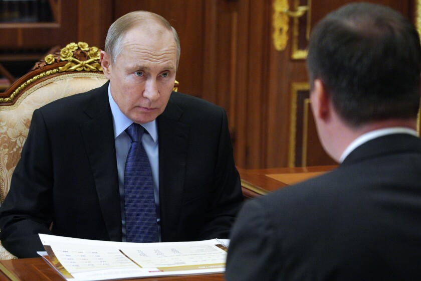 Russian President Vladimir Putin listens to Russian Agriculture Minister Dmitry Patrushev, back to a camera, during their meeting at the Kremlin in Moscow, Russia, Monday, April 5, 2021. (Alexei Druzhinin, Sputnik, Kremlin Pool Photo via AP)
