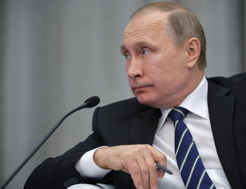 """Russian President Vladimir Putin attends a meeting with business leaders in Moscow, Russia, Wednesday, Jan. 20, 2016. President Vladimir Putin did not comment on the ruble's fall, although he said that Russia's economic foundations are """"fairly solid, despite all the external risks and difficulties."""" (Alexei Druzhinin/Sputnik, Kremlin Pool Photo via AP)"""