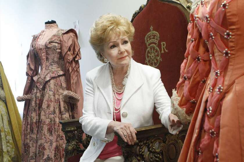 """Debbie Reynolds sits on the throne from the 1955 movie """"The Virgin Queen"""" in 2011, before an auction of items in her collection of memorabilia from classic movies."""