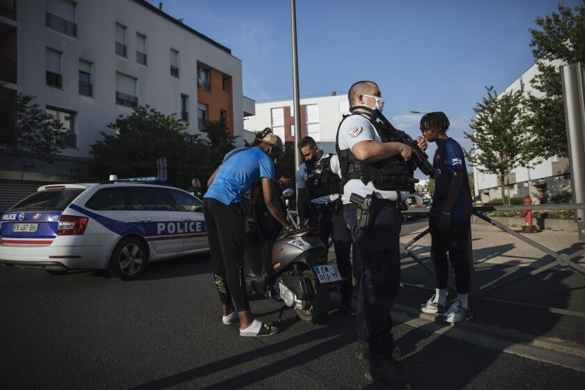 Police officers stop and search a motorbike rider and his passenger who did not wear any helmets, in the Paris suburb of Villiers-le-Bel, Tuesday, June, 15, 2021. In the run-up to France's presidential elections in 2022, crime and policing are again becoming hot-button issues. Some political opponents of President Emmanuel Macron argue that France is becoming an increasingly violent country. (AP Photo/Lewis Joly)