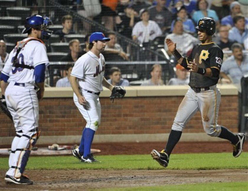 Pittsburgh Pirates' Ronny Cedeno (5) claps his hands as he crosses home plate in front of New York Mets catcher Josh Thole (30) and starting pitcher R.A. Dickey (43) after scoring the tying run in the eighth inning of a baseball game, Tuesday, May 31, 2011, in New York. (AP Photo/Kathy Kmonicek)