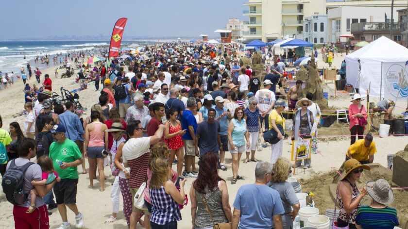 Crowds gather along Imperial Beach to view the sand castles as they are being sculpted.