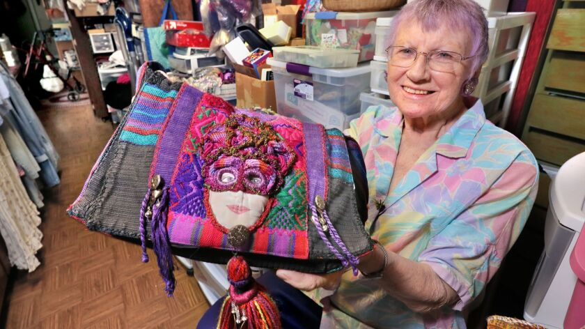 """Portrait of artist Rita Zerull with one of her purses she created featuring her intricate needlelace. She's in her crowded work studio she calls her """"parts department."""""""