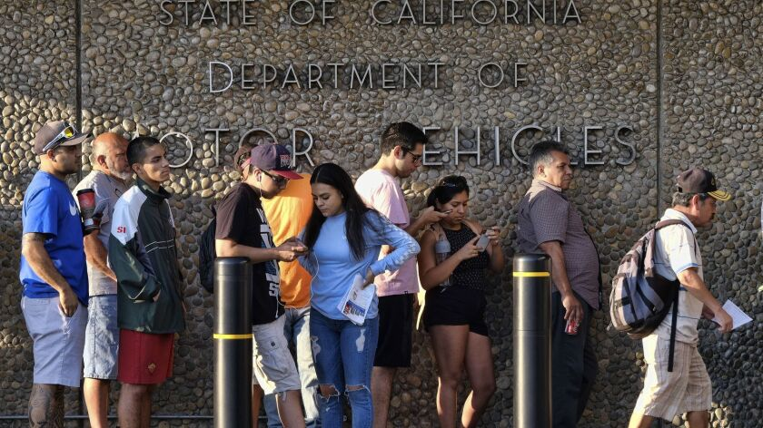 FILE - In this Aug. 7, 2018, file photo, people line up at the California Department of Motor Vehicl