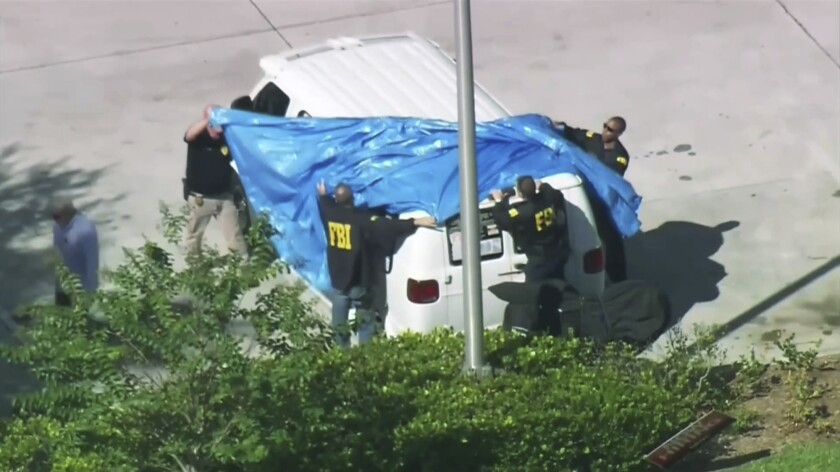 FBI agents cover a van parked in Plantation, Fla., on Oct. 26. Investigators have been examining the vehicle in connection with package bombs that were sent to high-profile critics of President Trump.