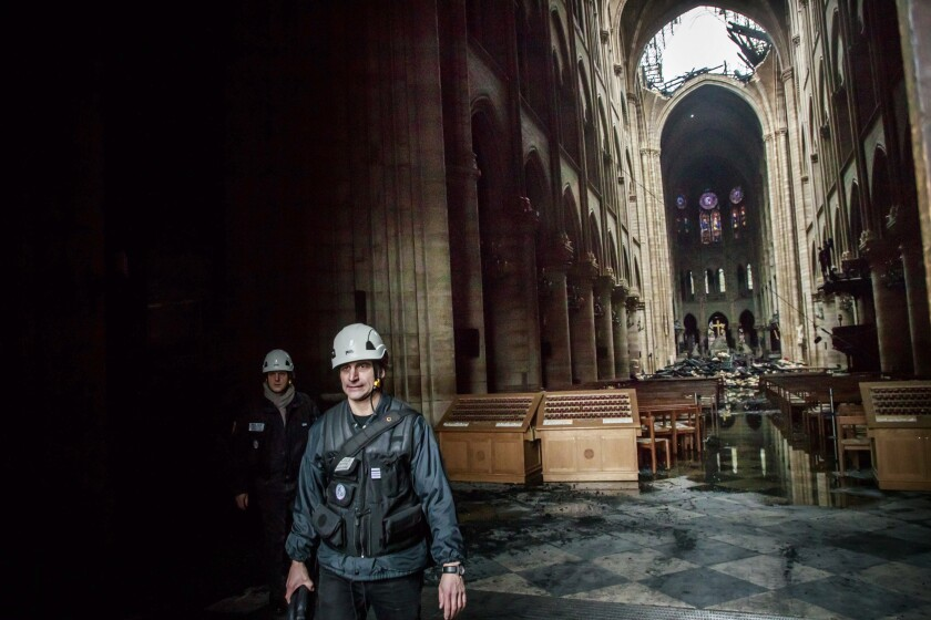 A man walks nside the damaged Notre Dame cathedral in Paris, Tuesday, April 16, 2019. Firefighters d