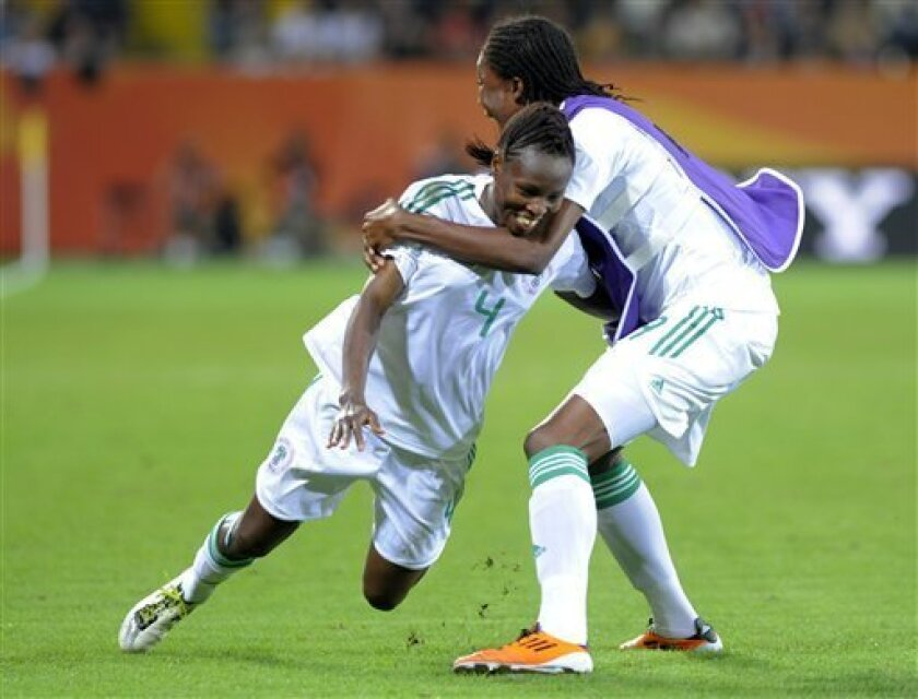 Nigeria's Perpetua Nkwocha, left, celebrates scoring her side's first goal during the group A match between Canada and Nigeria at the Women's Soccer World Cup in Dresden, Germany, Tuesday, July 5, 2011. (AP Photo/Jens Meyer)