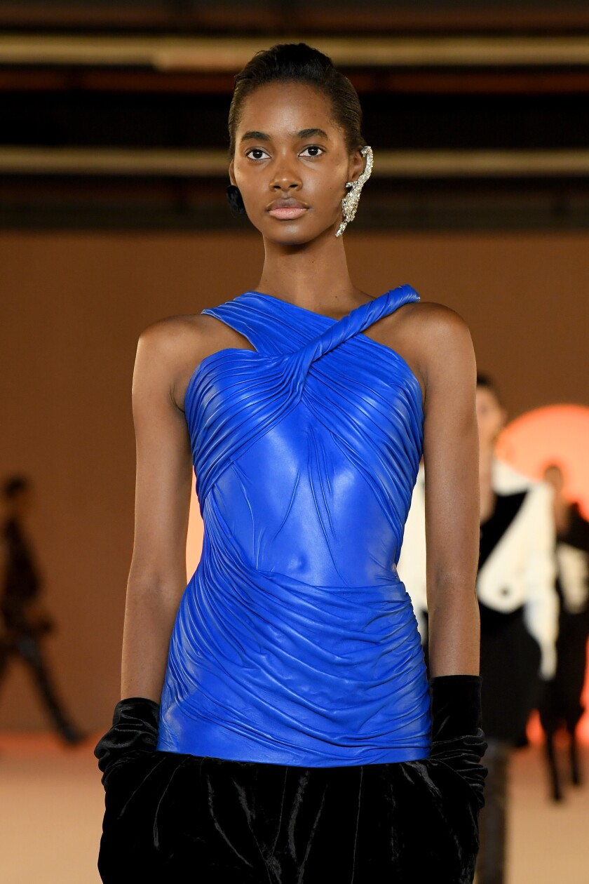A model in an electric blue molded-leather bustier top and black velvety gloves.
