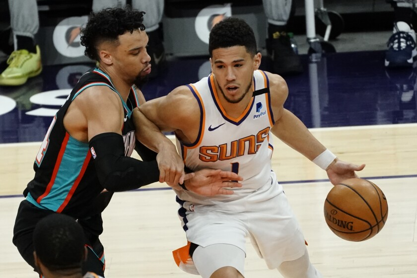 Phoenix Suns guard Devin Booker (1) is pressured by Memphis Grizzlies guard Dillon Brooks during the first half of an NBA basketball game Monday, March 15, 2021, in Phoenix. (AP Photo/Rick Scuteri)