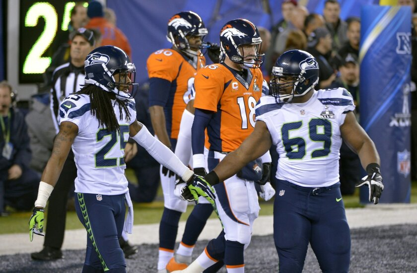 Seattle Seahawks' Richard Sherman, left, and Clinton McDonald, right, react in front of Denver Broncos' Peyton Manning (18) after a safety during the first half of the NFL Super Bowl XLVIII football game Sunday, Feb. 2, 2014, in East Rutherford, N.J. (AP Photo/Bill Kostroun)