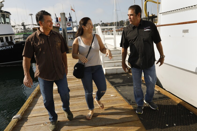 A woman and two men walk along a pier next to a boat in San Pedro.