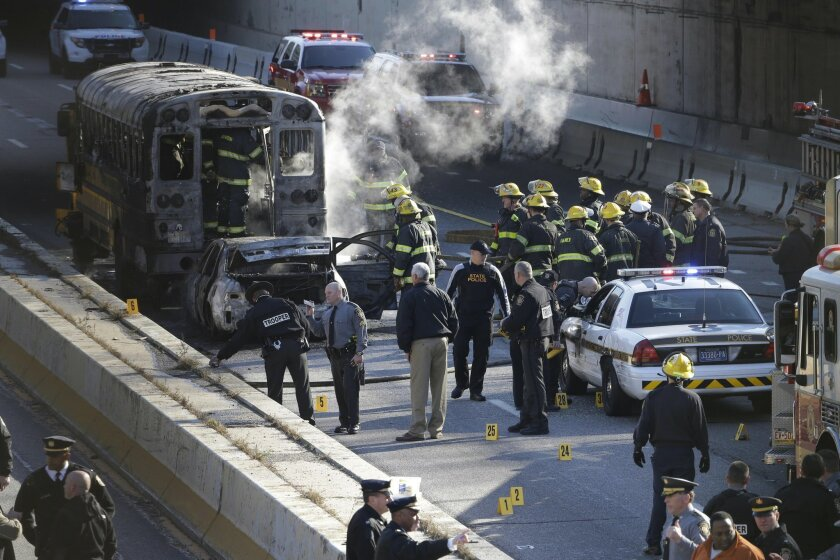 Investigators and firefighters work the scene of a fire and shooting Tuesday, Nov. 24, 2015, in Philadelphia. A Pennsylvania state police trooper has been shot in the shoulder after a fiery crash along Interstate 676. (AP Photo/Matt Rourke)