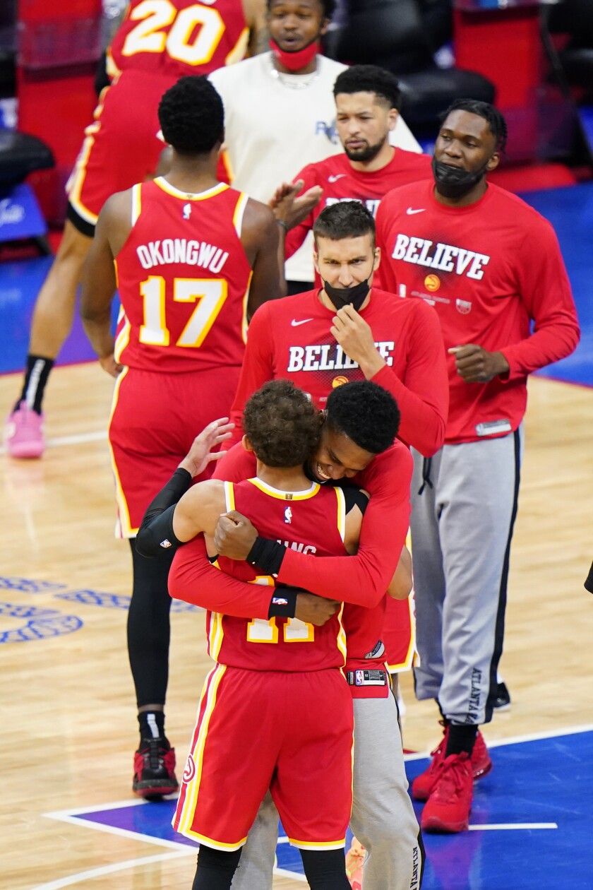 Atlanta Hawks' Trae Young, left, celebrates with teammates after the Hawks won Game 5 in a second-round NBA basketball playoff series against the Philadelphia 76ers, Wednesday, June 16, 2021, in Philadelphia. (AP Photo/Matt Slocum)