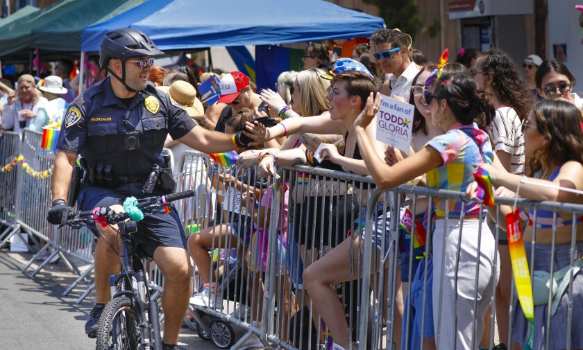 San Diego Police Officer Saum Poorsaleh high fives spectators during the annual San Diego Pride Parade in Hillcrest.