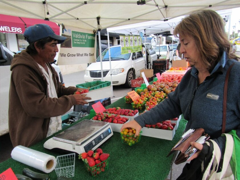 Trish Watlington of Mount Helix buys some tomatoes earlier this year at the La Mesa Certified Farmers Market. The city is mulling over how to continue its popular Friday market after complaints from some businesses that they are losing money. Meanwhile, Grossmont Center is starting its own farmers market on Wednesdays.