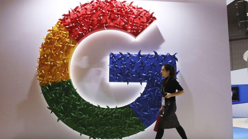 A woman walks past the Google logo at an expo in November.
