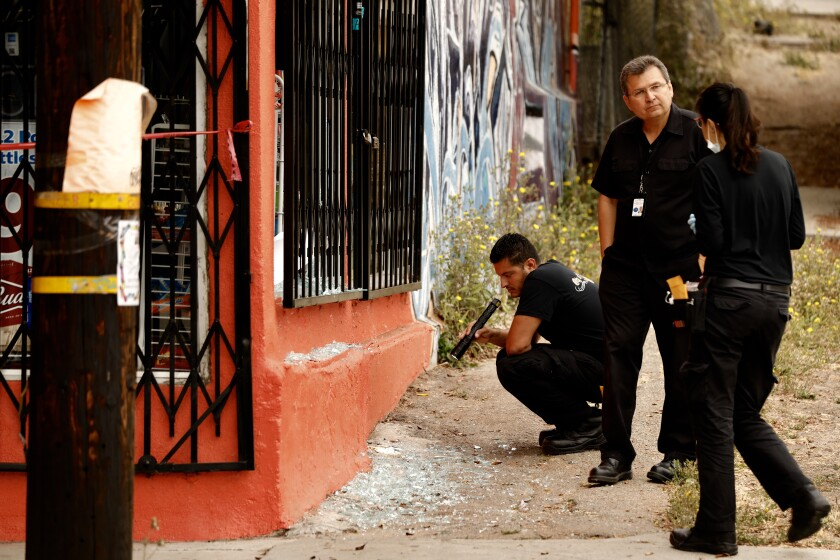 LAPD investigators from Force Investigation Division inspect a building with bullet holes near the scene of an officer involved shooting at Alhambra Ave and Belleglade in the El Sereno neighborhood