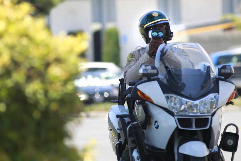 A Los Angeles County Sheriff's Deputy aims his laser at a speeding motorist in La Mirada in 2012.