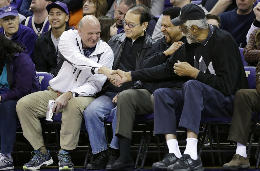 """Steve Ballmer, left, shakes hands with former NBA players Bill Russell, right, and """"Downtown"""" Freddie Brown."""