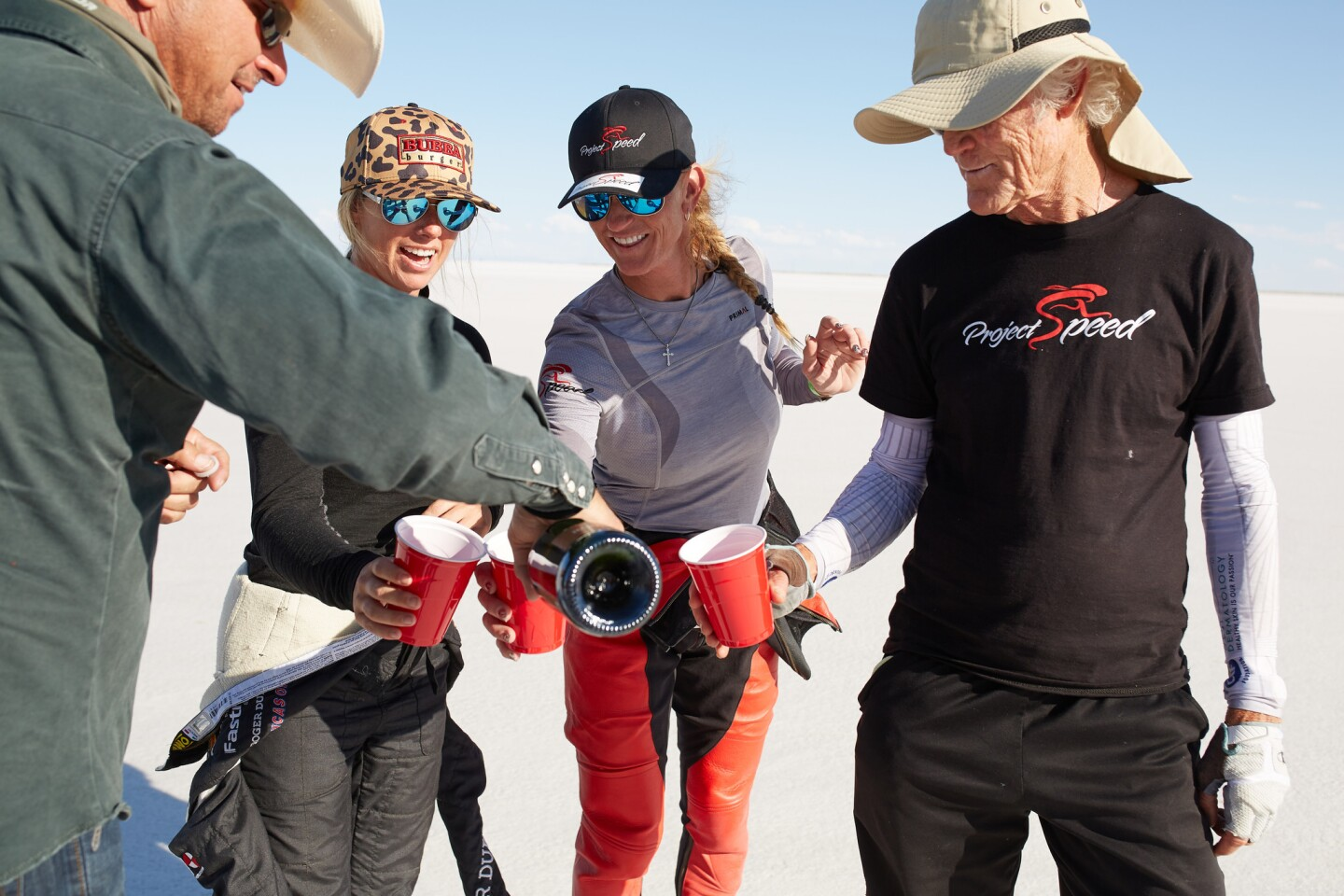 Denise Mueller-Korenek, second from right, celebrates with champagne her record-breaking ride to set the paced bicycle speed record of 183.9 mph on Sunday in Utah. She's pictured with her husband Chris Korenek, left, pace car driver Shea Holbrook, second from left, and cycling coach John Howard, right.