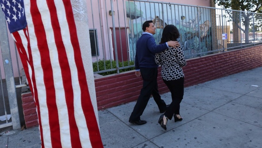 LOS ANGELES, CA MARCH 3, 2015 -- Jose Huizar and his wife Richelle walk out after casting their vot
