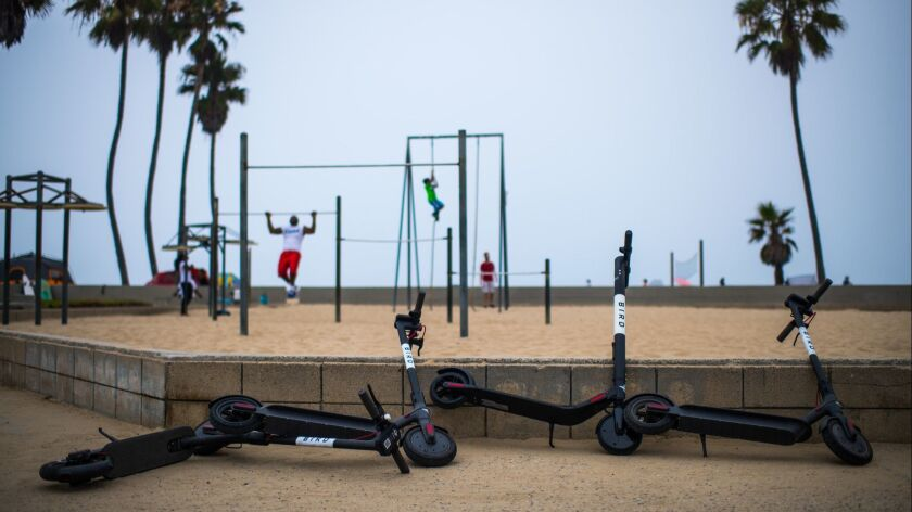 VENICE, CA - July 25, 2018 Bird electric scooters sit discarded along the Venice Beach Boardwalk in